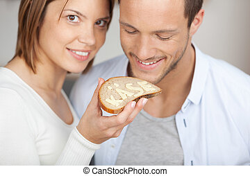 Smiling couple holding a slice of bread and cheese