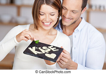 Smiling couple holding a stone slab with cheese