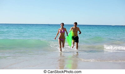 Smiling couple holding an air mattress on the beach