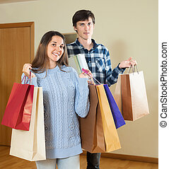 Smiling couple holding purchases in hands