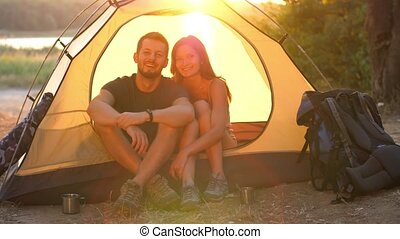 Smiling couple in a tent - Young couple resting in camping...