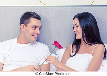 smiling couple in bed with flower