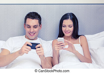 smiling couple in bed with smartphones