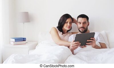 smiling couple in bed with tablet pc computer