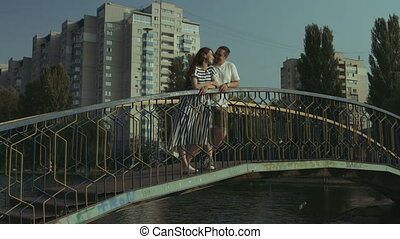 Smiling couple in love embracing on the bridge