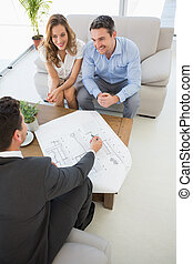 Smiling couple in meeting with a financial adviser - High...