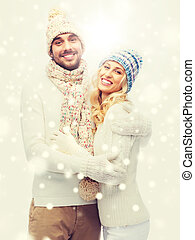 smiling couple in winter clothes hugging - winter, fashion,...
