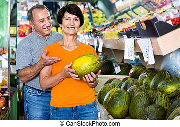 Smiling couple is choosing green melon in the supermarket.