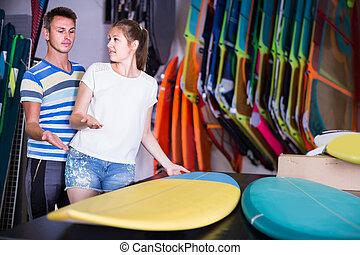 couple is choosing surfboard in nautical shop.