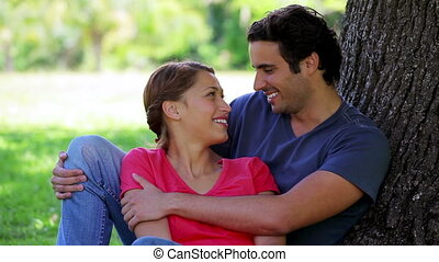 Smiling couple leaning against a tree in a parkland