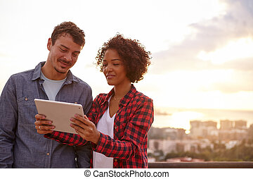 Smiling couple looking at a tablet