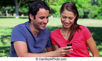 Smiling couple looking at a text on a cellphone