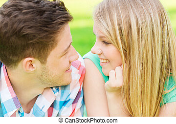 smiling couple looking at each other in park