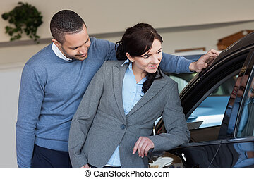 Smiling couple looking inside a car