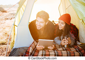 Smiling couple lying in tent and using tablet computer -...