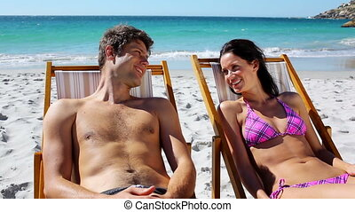 Smiling couple lying on deck chairs on the beach