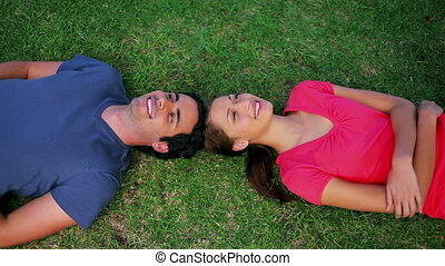 Smiling couple lying on the grass in a parkland