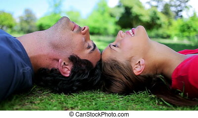 Smiling couple lying together on the grass