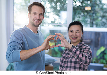 Smiling couple making heart shape with hands