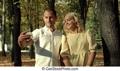 Smiling couple making selfie in autumn park