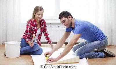 smiling couple measuring wallpaper - repair, building and...