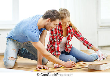 smiling couple measuring wood flooring - repair, building...
