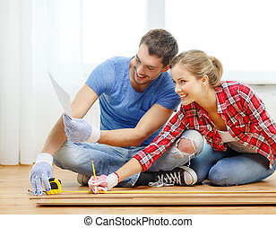smiling couple measuring wood flooring - repair, building...
