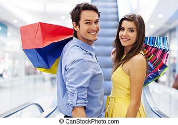 Smiling couple on escalator in shopping mall