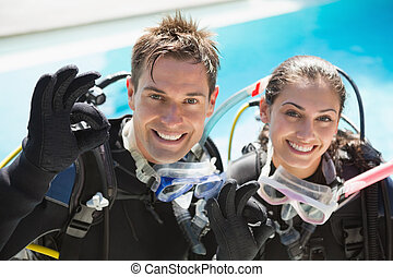 Smiling couple on scuba training in swimming pool showing ok...