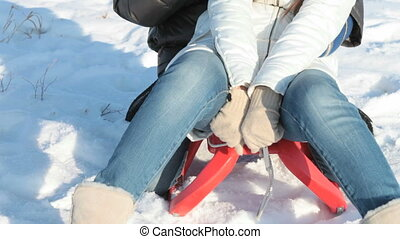 Smiling couple on sledge - Young people sitting on sled and ...