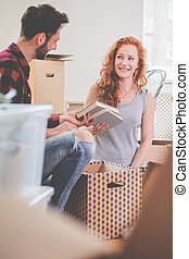 Smiling couple packing stuff into carton boxes while moving-out