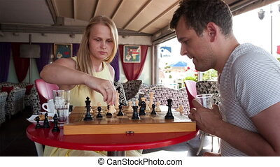 Smiling couple playing a game of chess