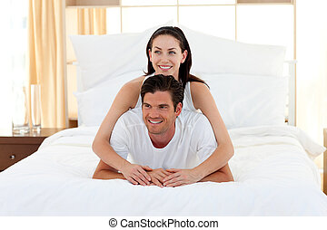 Smiling couple playing on bed together