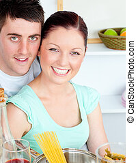 Smiling couple preparing spaghetti in the kitchen