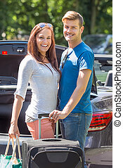 Smiling Couple Putting Luggage In A Car Trunk