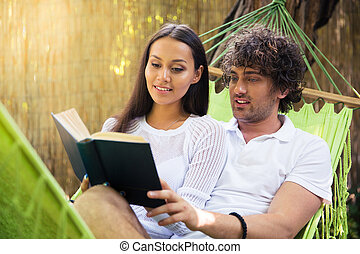 Smiling couple reading book together outdoors