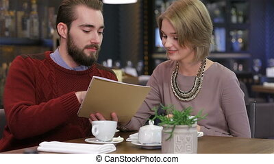 Smiling couple reading menu and choosing meal - Celebrating...