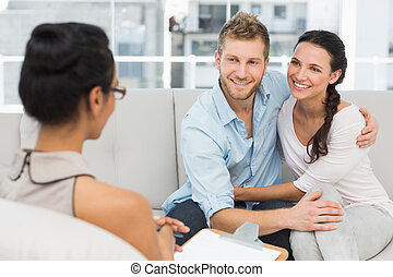 Smiling couple reconciling at therapy session in therapists office