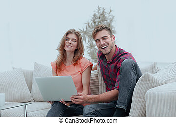 smiling couple resting at home, sitting on the couch.