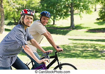 Smiling couple riding bicycles in park