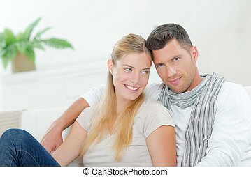 Smiling couple sat on sofa