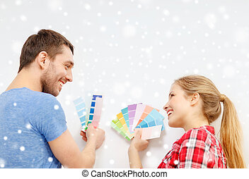 smiling couple selecting color from samples