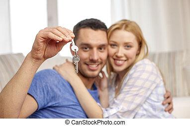 smiling couple showing keys over room background