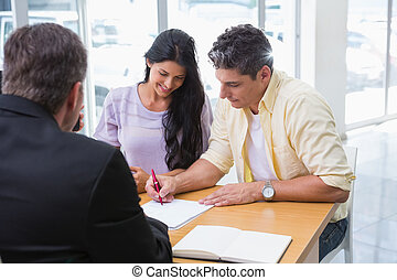 Smiling couple signing a contract