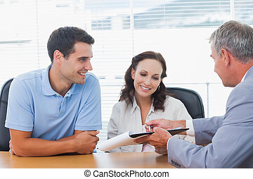 Smiling couple signing contract with real estate agent in...