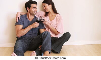 Smiling couple sitting down while clinking their glasses