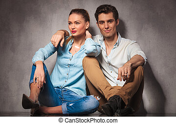 smiling couple sitting embraced on the floor
