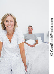 Smiling couple sitting on opposite ends of bed