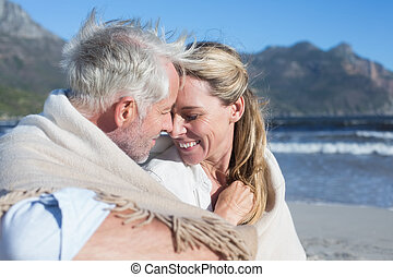 Smiling couple sitting on the beach under blanket