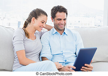 Smiling couple sitting on the couch using tablet pc at home...